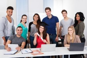 27394263 - portrait of university student holding degree with classmates standing in classroom